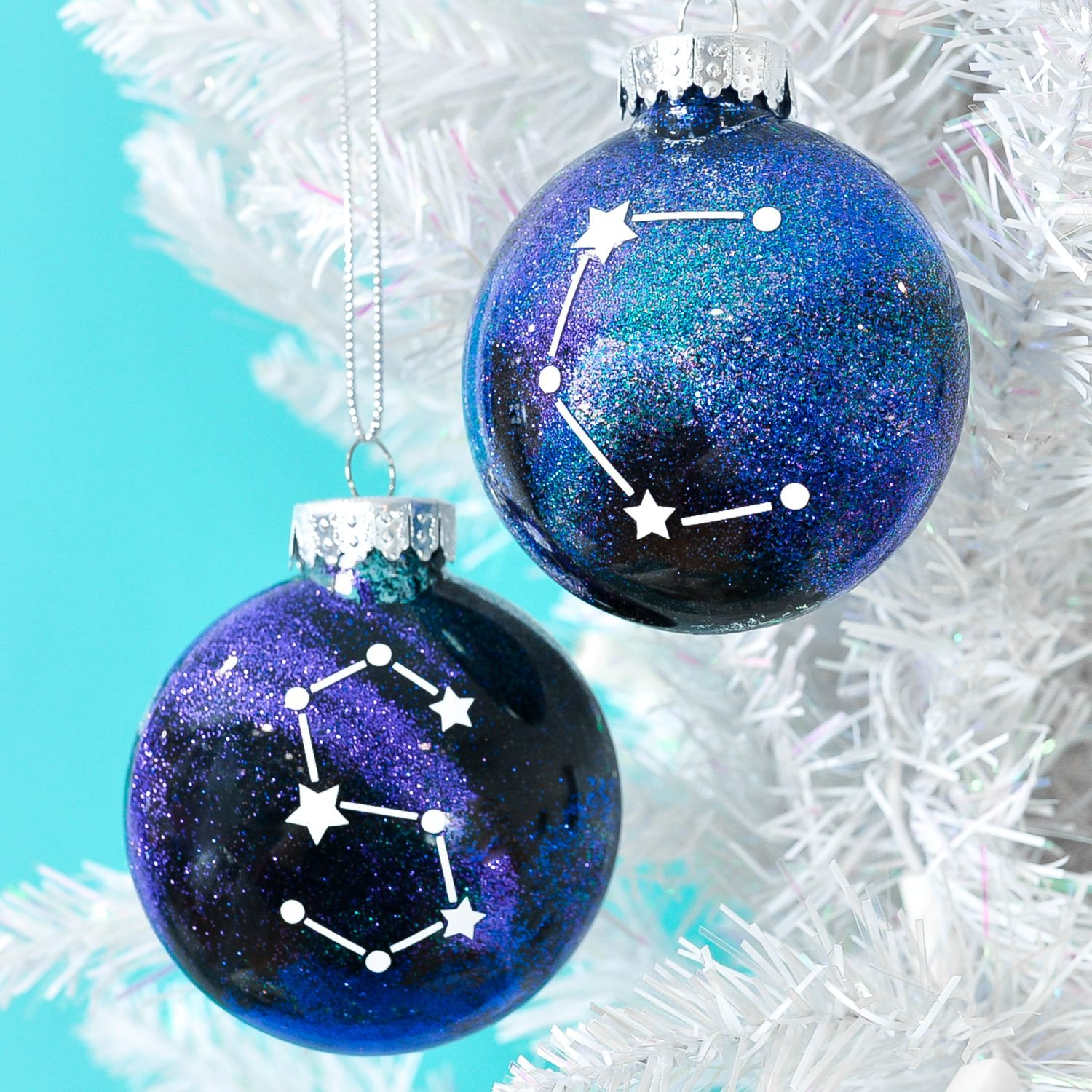 Finished constellation glitter ornaments hanging from white Christmas tree