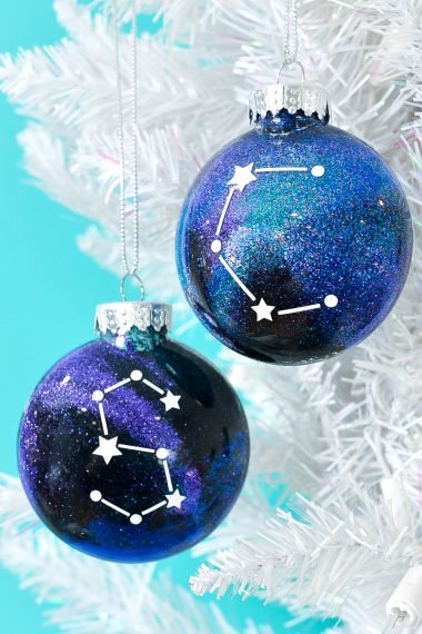Finished constellation glitter ornaments hanging from white Christmas tree.