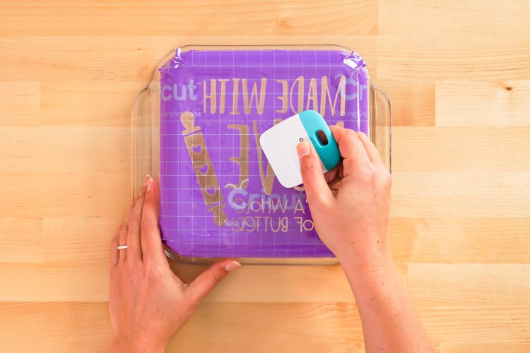 Hands adhering stencil to the bottom of the dish.