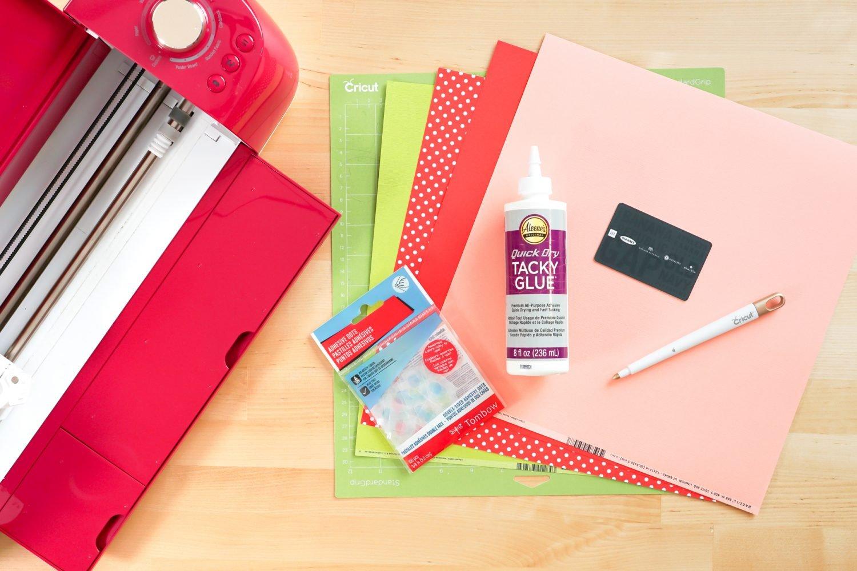 Supplies for gift card holder: Cricut, paper, glue, scoring stylus, cricut mat, glue dots, gift card