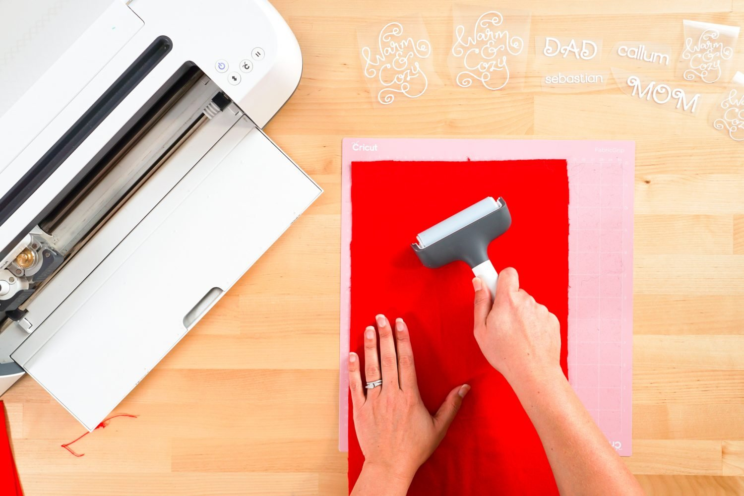 Hands using a brayer to put red flannel on Cricut mat