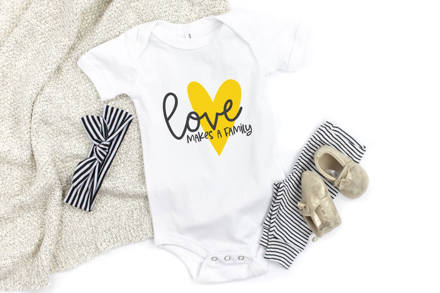 Love Makes a Family decal on onesie with baby shoes, headband, and blanket