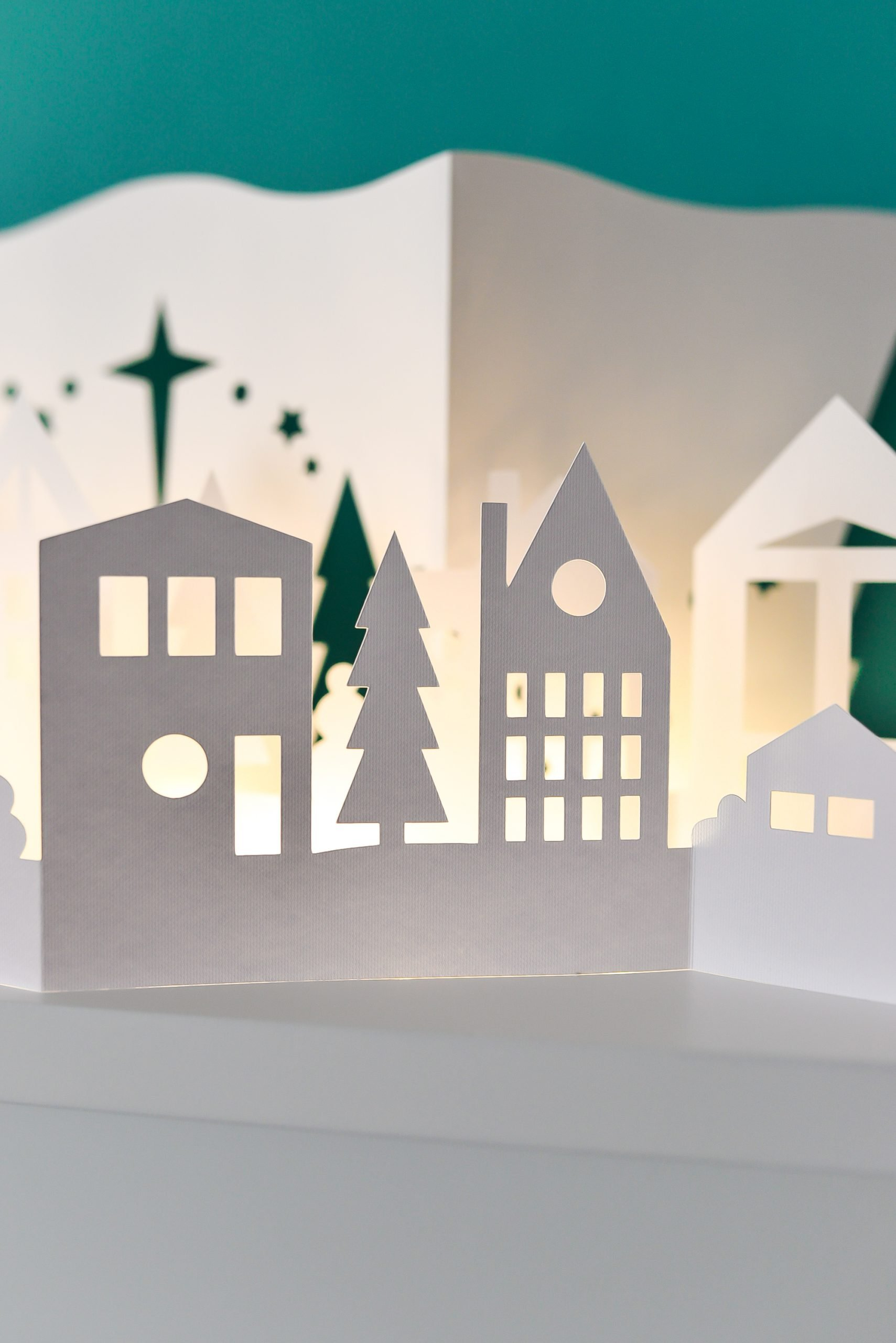 Papercut Christmas Village illuminated with fairy lights