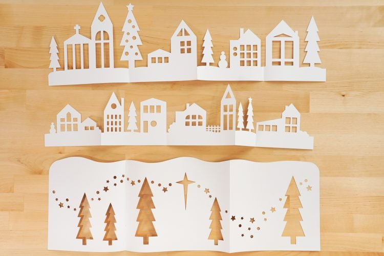 Three folded layers of the papercut Christmas village