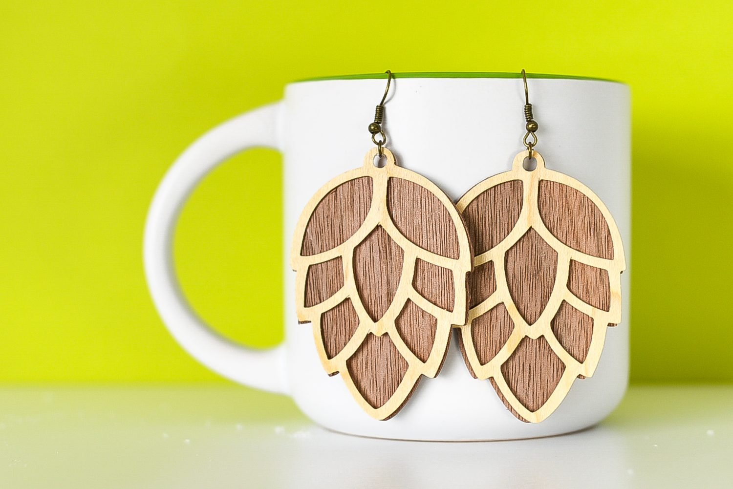 Finished pinecone earrings hanging from a mug with a green background.