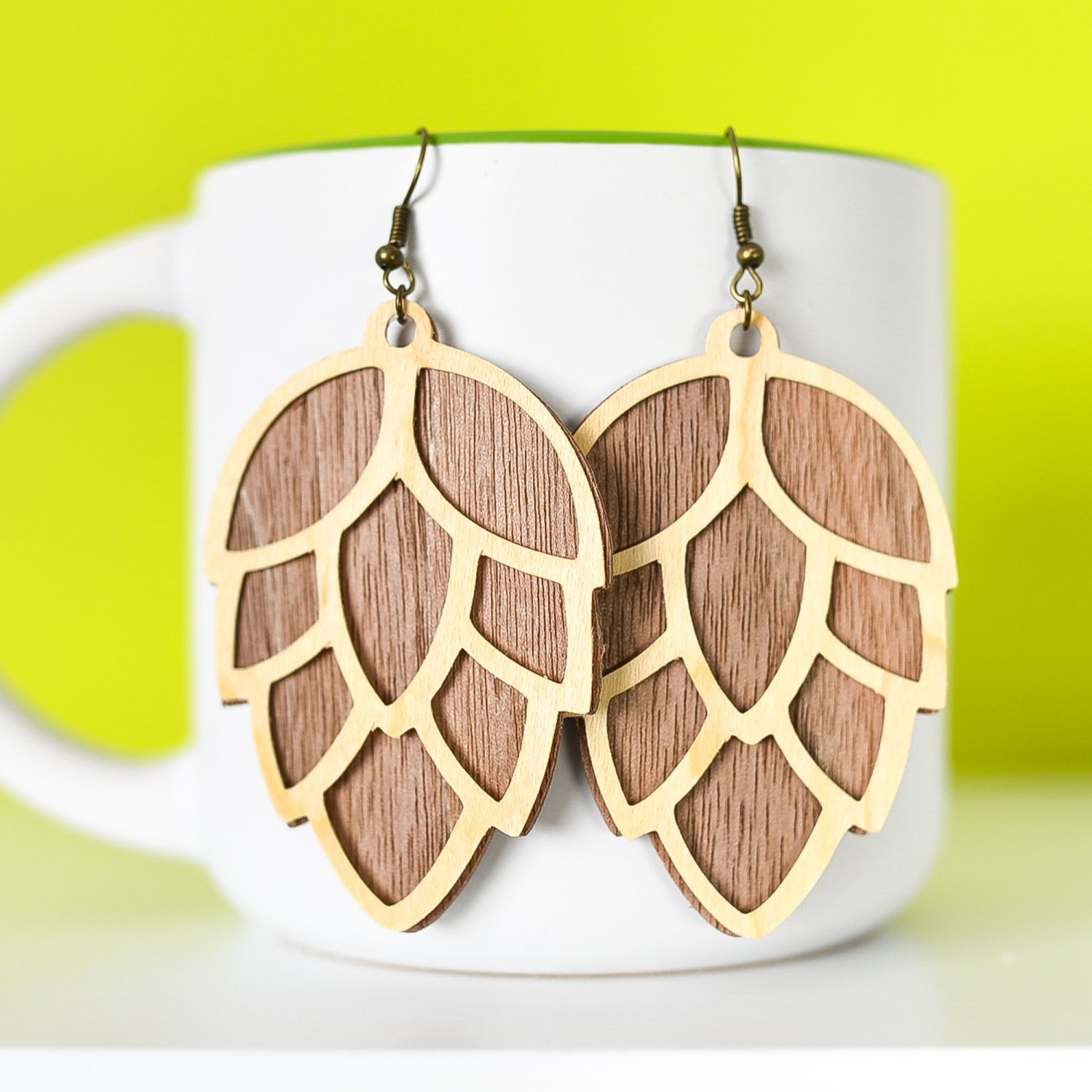 Close up of finished pinecone earrings hanging from a mug with a green background.
