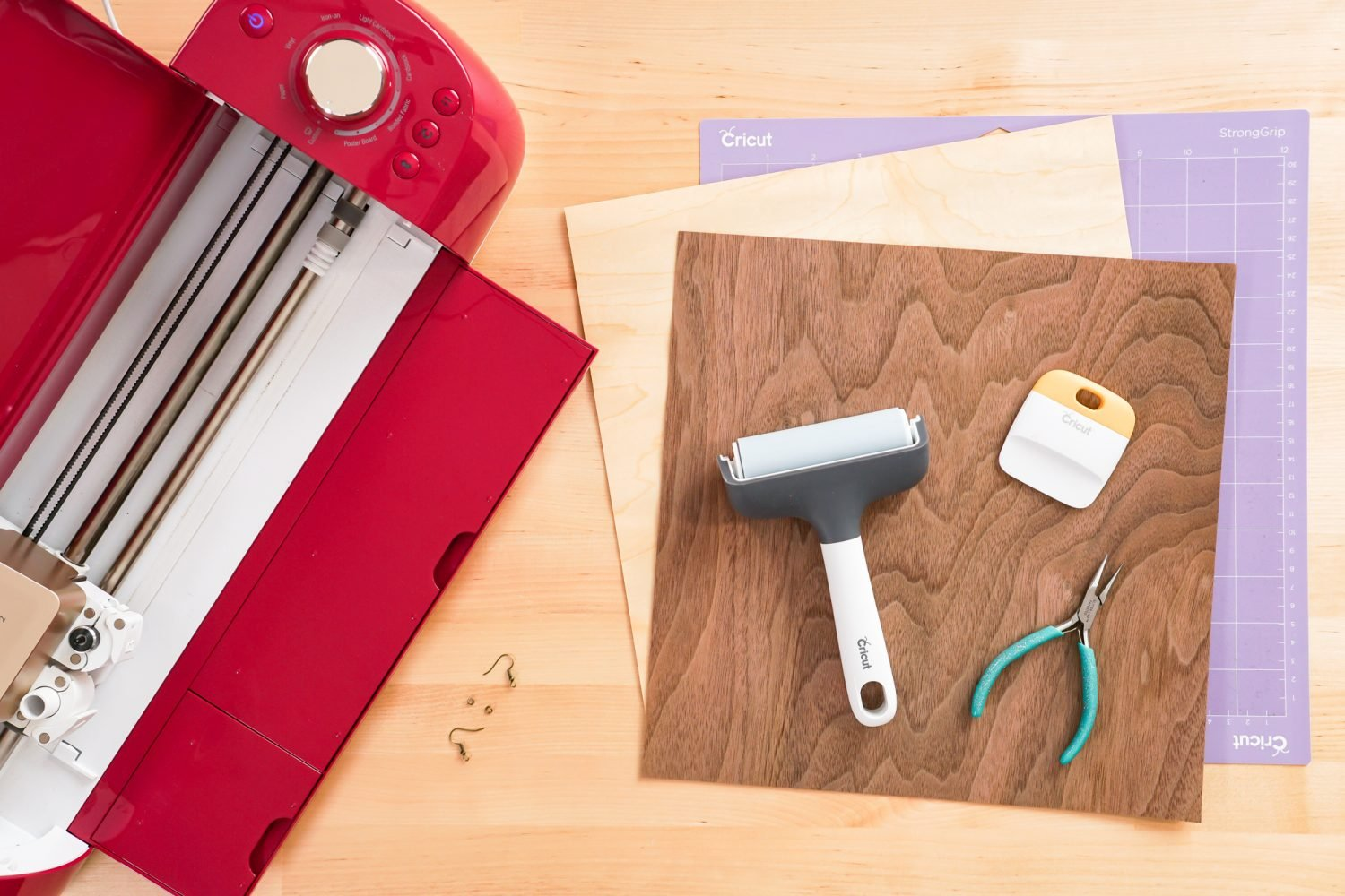 Supplies needed for this project: Cricut, purple StrongGrip mat, two colors of Cricut veneer, brayer, scraper, jewelry pliers, earring findings.