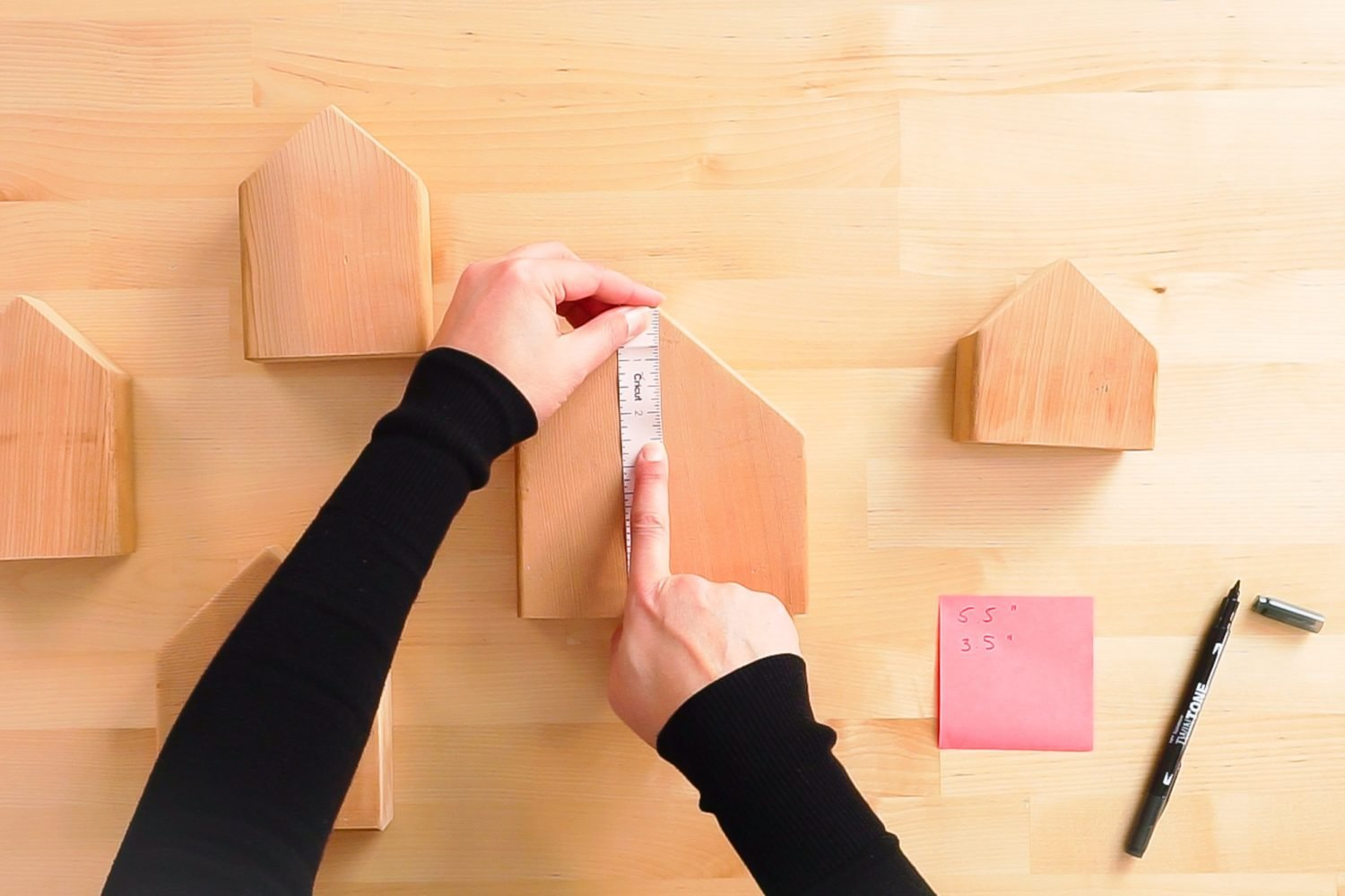 Hands measuring houses