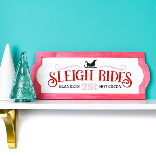Sleigh Rides sign on white shelf with blue background and Christmas tree decor