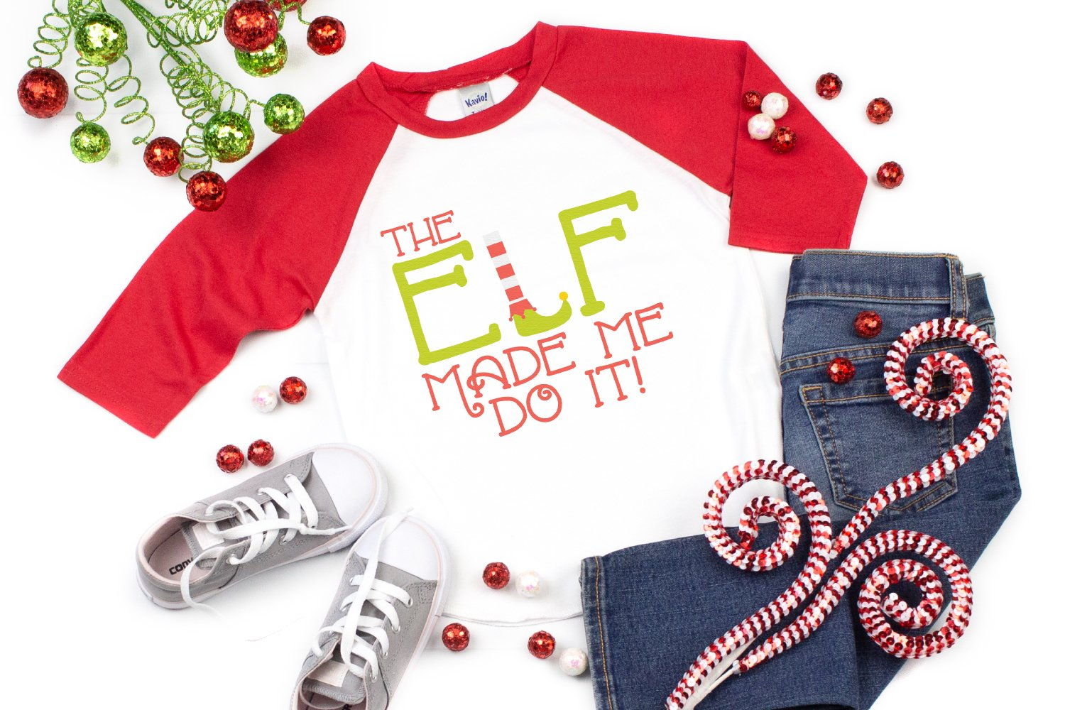 The Elf Made Me Do It SVG on a red and white raglan shirt