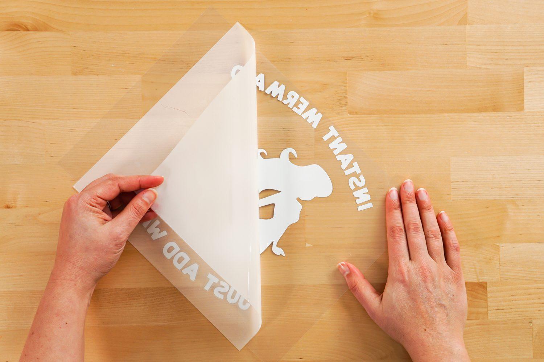 Hands peeling back HTV liner