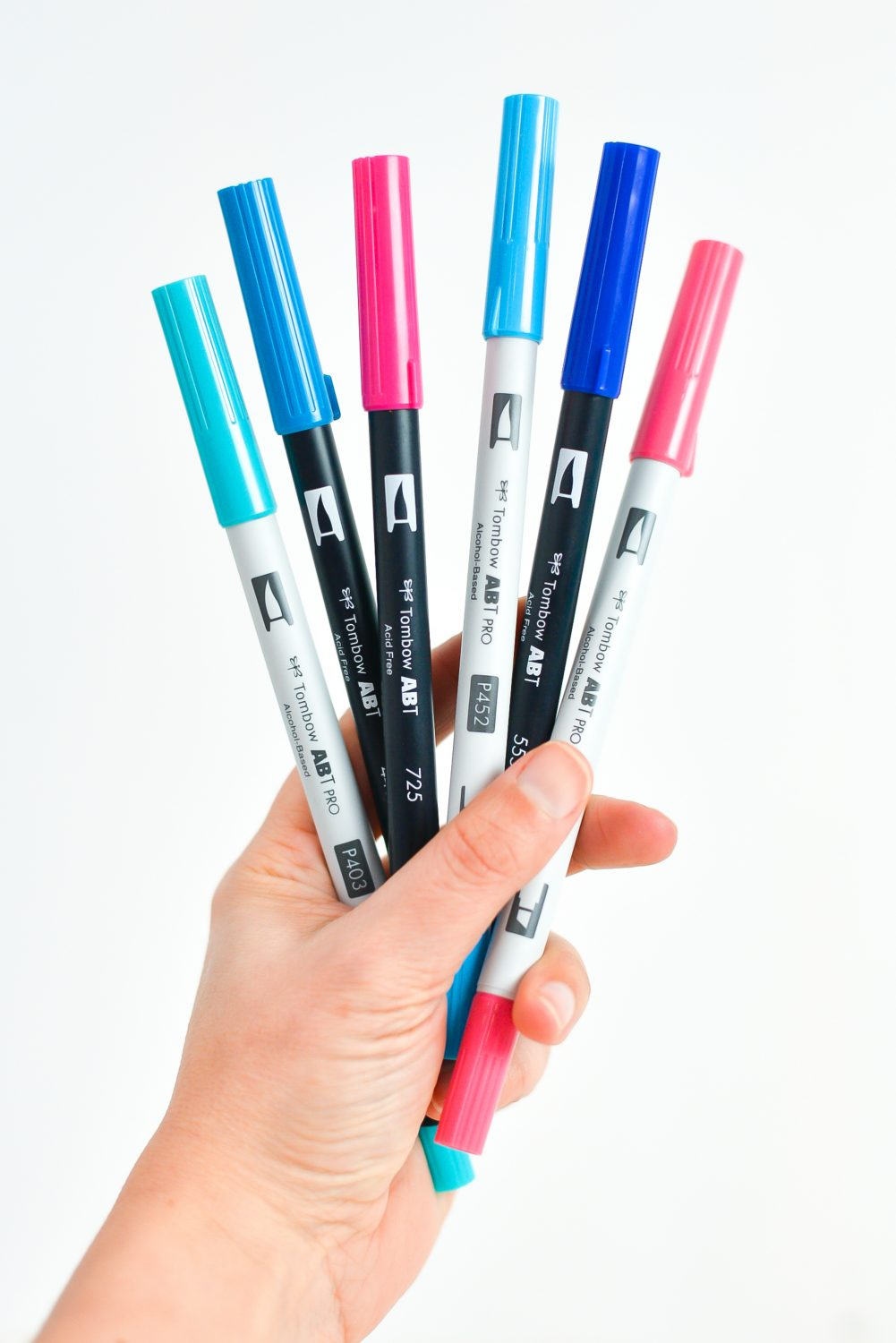 Hand holding a variety of Tombow pens