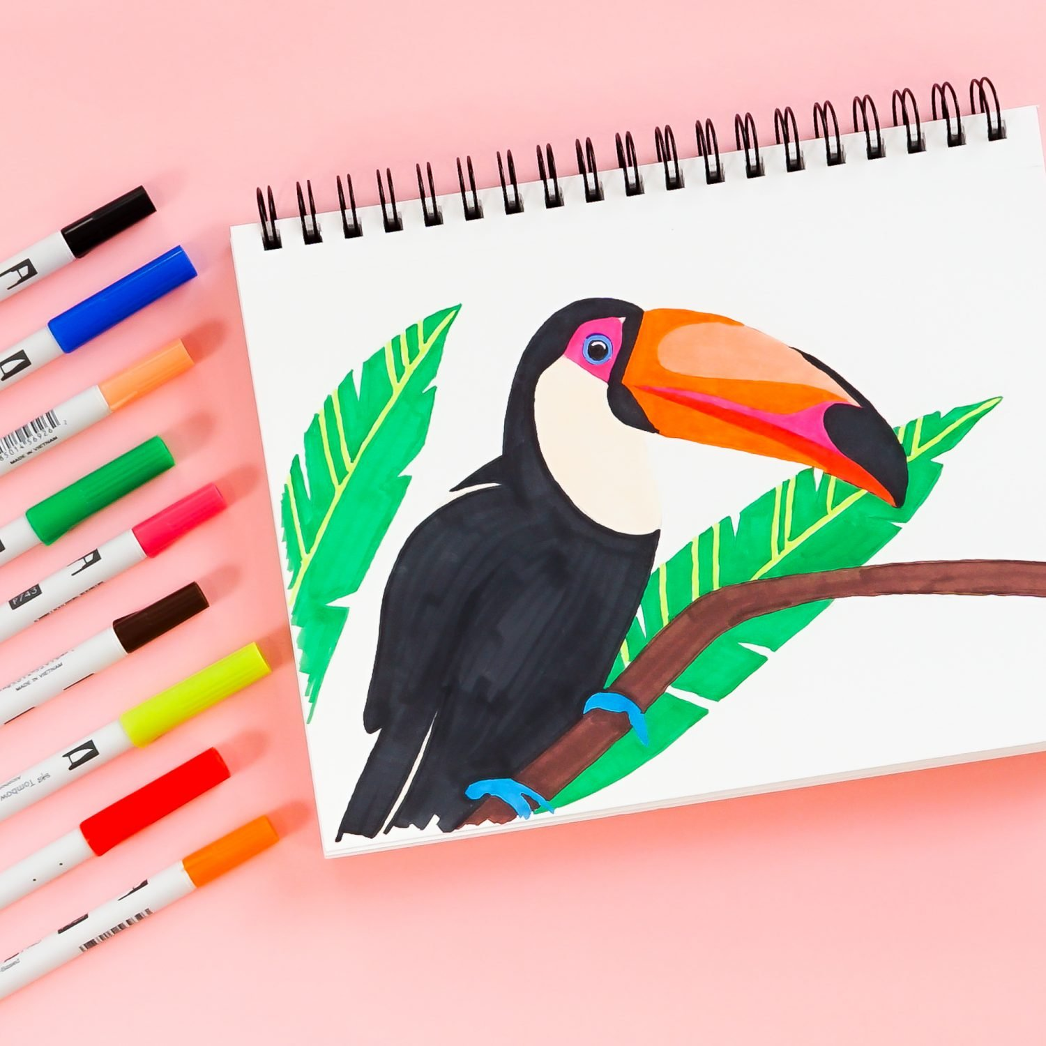 Toucan illustration with Tombow ABT PRO Markers surrounding the drawing