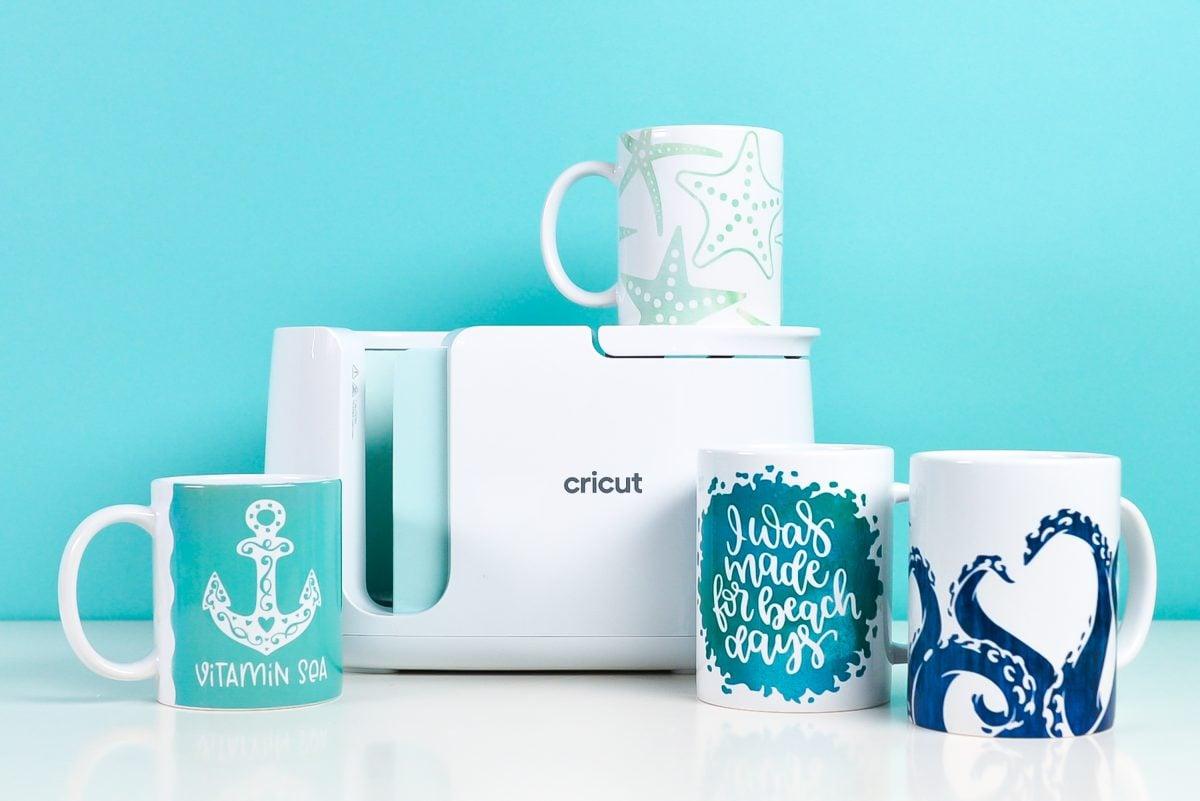 Cricut Mug Press with four sea-themed mugs